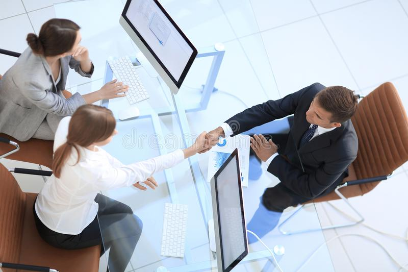 View from the top. handshake the senior Manager and the employee above the Desk stock image