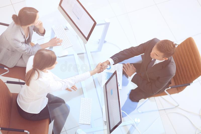 View from the top. handshake the senior Manager and the employee above the Desk stock images