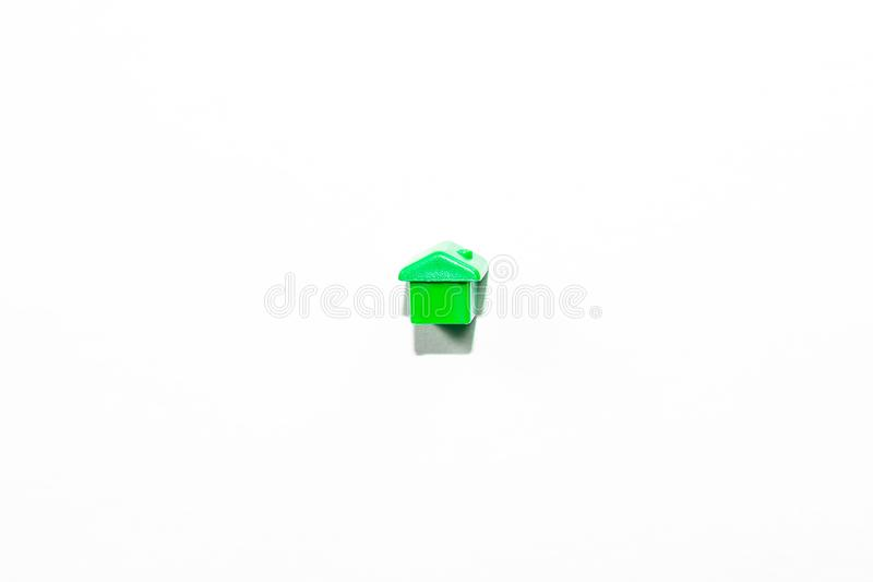 View from the top of the plastic miniature house in green as a part of the monopoly game on a white background. View from the top of the plastic miniature house stock photography