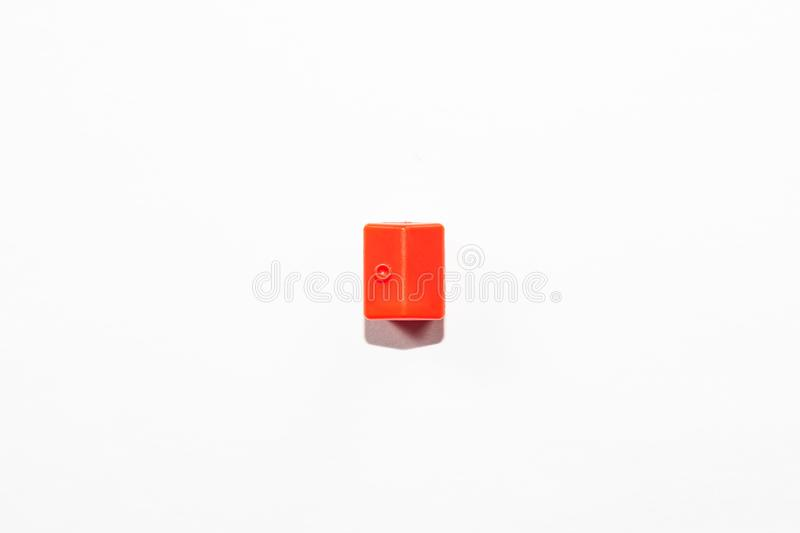 View from the top of the plastic miniature house in red as a part of the monopoly game on a white background. View from the top of the plastic miniature house in royalty free stock photography
