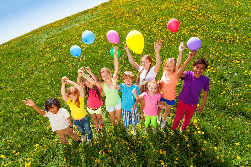 View from top of standing children with balloons stock photography