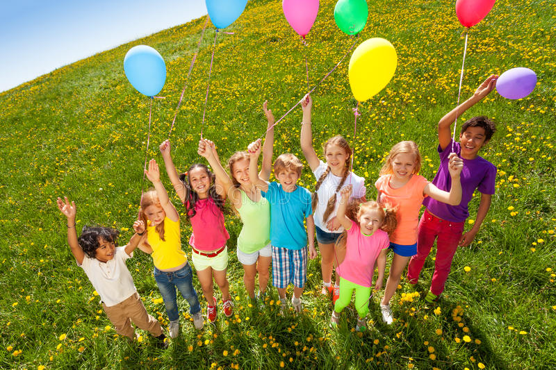 View from top to standing kids with balloons. On green meadow royalty free stock photography