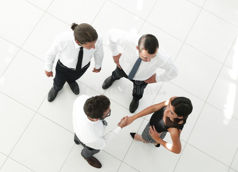 View from the top.welcome colleagues shaking hands in office royalty free stock photography