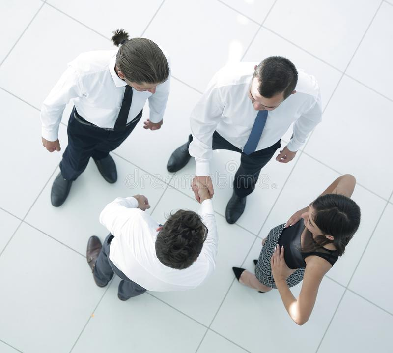 View from the top.welcome colleagues shaking hands in office stock photography