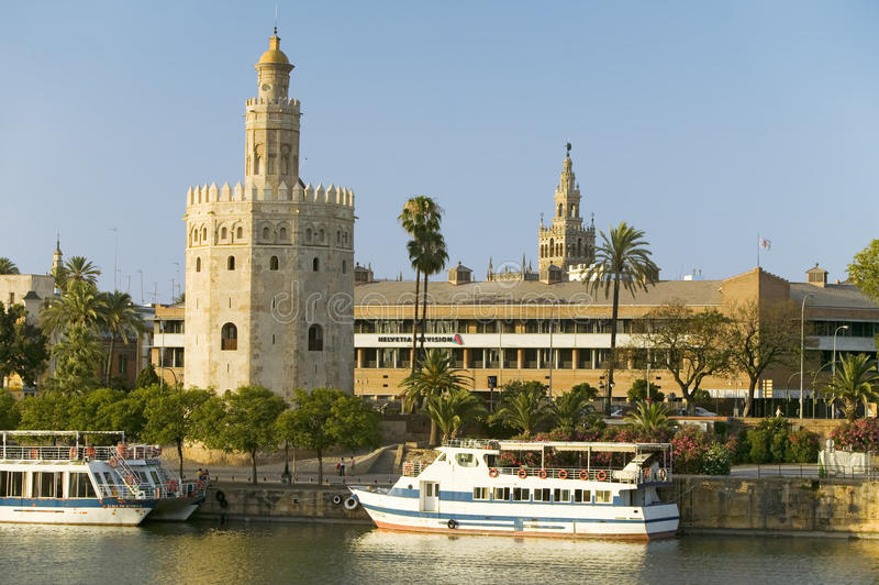 View of the tour boats and octagonal tower of Torre del Oro makes golden reflection on Canal de Alfonso of Rio Guadalquivir stock photo