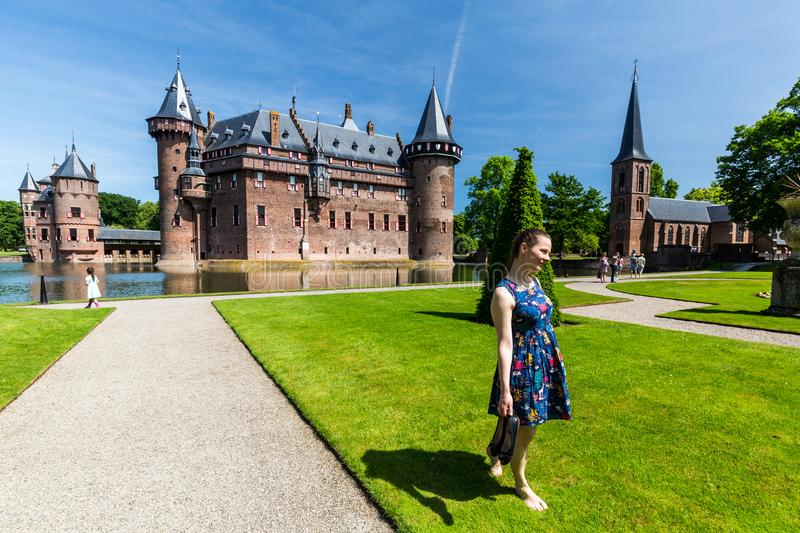 View of a tourist girl in the gardens of the De Haar Castle. DE HAAR CASTLE, NETHERLANDS - MAY 28, 2017: View of a tourist girl in the gardens of the De Haar royalty free stock photography