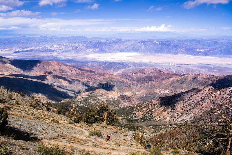 View towards Badwater Basin from the trail to Telescope Peak; hikers in the foreground; Death Valley National Park, California royalty free stock images