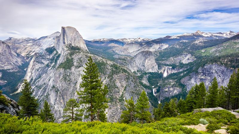 View towards Half Dome; Vernal Fall, Nevada Fall and Liberty Dome visible on the right; snow capped mountains in the background; stock images