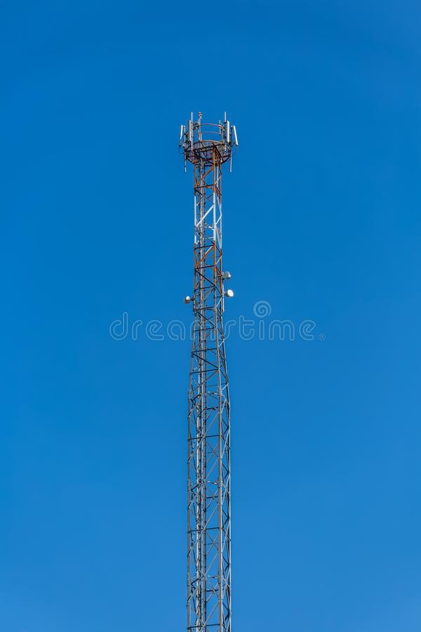 View of a tower with telecommunications antennas, details of the metallic structure and equipment. Blue sky as background stock photography