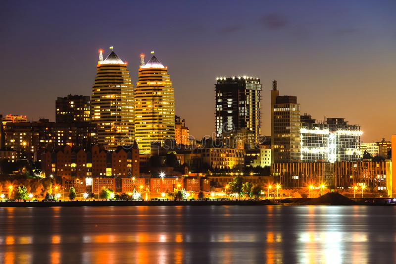 View of the towers, skyscrapers and buildings in Dnepr city at night, lights reflected on the river Dnieper, Ukraine. stock image