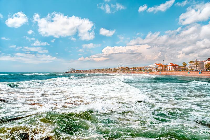 View on the town and the beach from sea with big waves, Sitges, Spain royalty free stock image