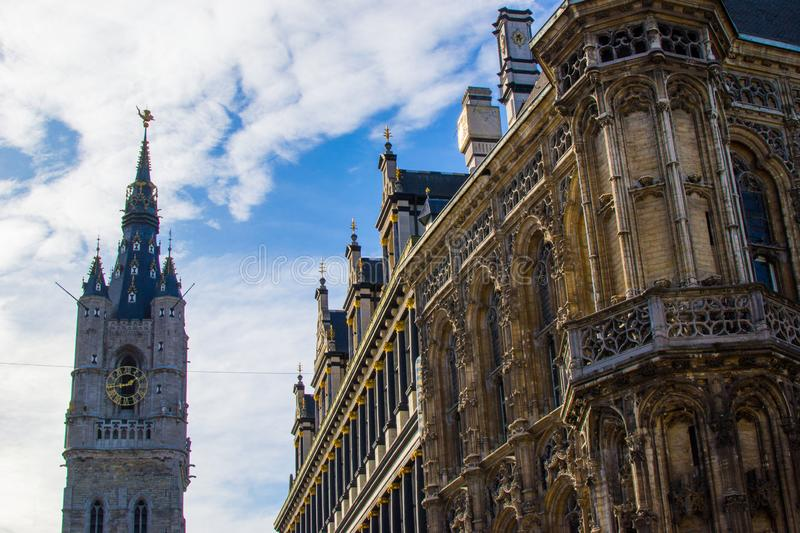 View of the Town Hall of Ghent, Belgium, Europe, on the right side and the Belfry Bell tower at the background stock photo