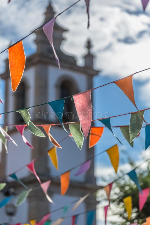 View of traditional decoration of religious festivals on the villages, with colored triangles of paper hanging in threads, church. Tower on background, in stock photo