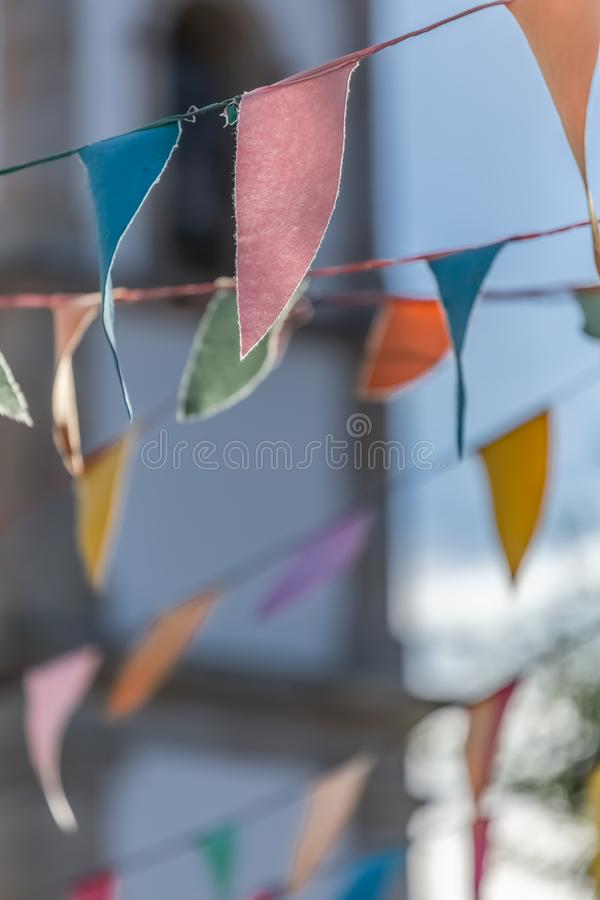 View of traditional decoration of religious festivals on the villages, with colored triangles of paper hanging in threads, church. Tower on background, in stock photography