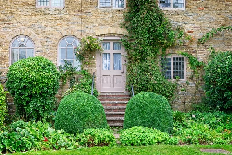 A rear view of an English country house from the garden. A view of a traditional English country house, showing the rear door leading from the steps to the stock photo