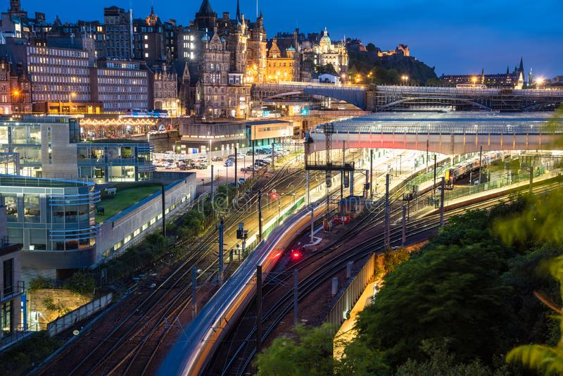 View of a train in motion leaving a train station at night. View from above of Edinburgh train station with a train leaving the platform at night. Edinburgh old royalty free stock photos