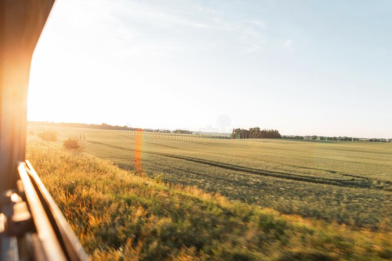 View from the train window in the motion of the countryside and the blue sky on a bright sunny warm summer day at sunset. royalty free stock photography