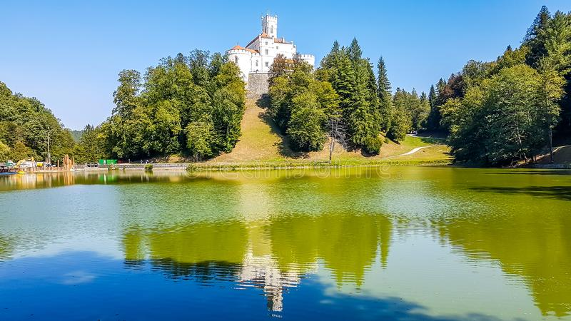 Varazdin - Castle on the hill. A view on Trakoscan castle from the lake side. Castle is located on a small hill and well hidden in between the trees. The lake in royalty free stock photography