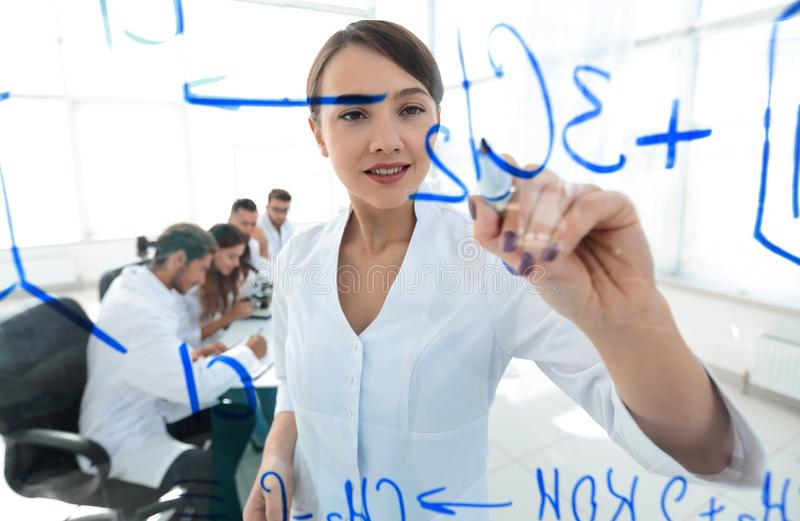 View through the transparent Board. female scientist makes a report to colleagues. Concept of research stock photos