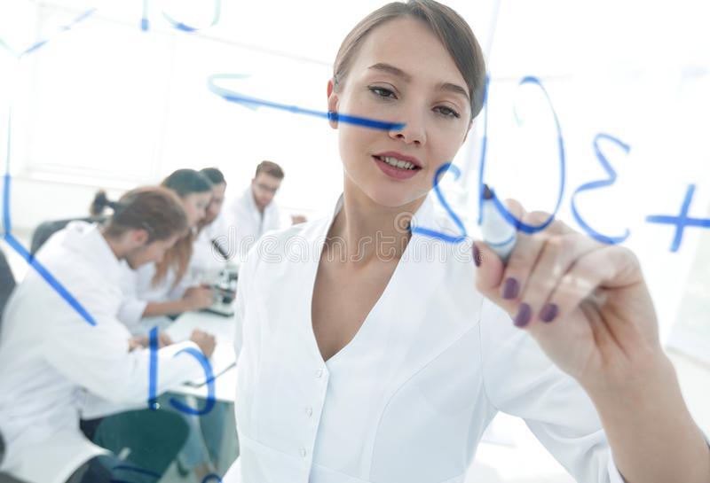 View through the transparent Board. female scientist makes a report to colleagues. Concept of research stock photo