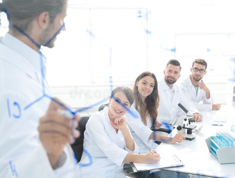 View through the transparent Board. a scientist makes a report. stock image
