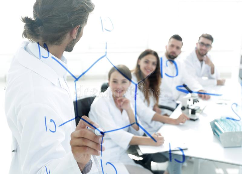 View through the transparent Board. a scientist makes a report. The concept of education stock photography