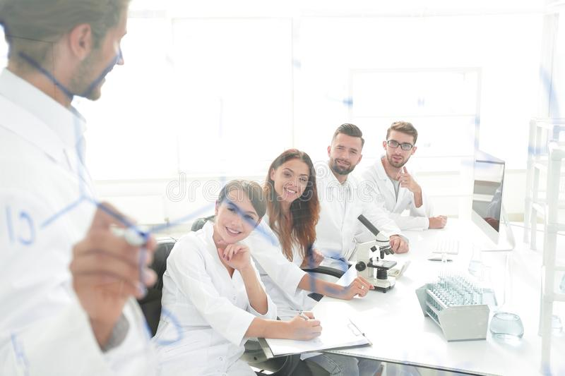 View through the transparent Board. a scientist makes a report. royalty free stock photography