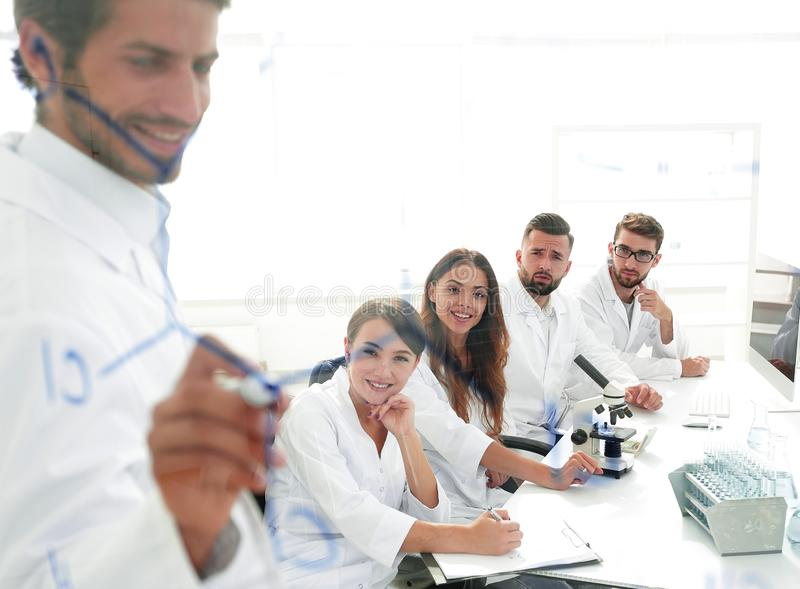 View through the transparent Board. a scientist makes a report. The concept of education stock photo