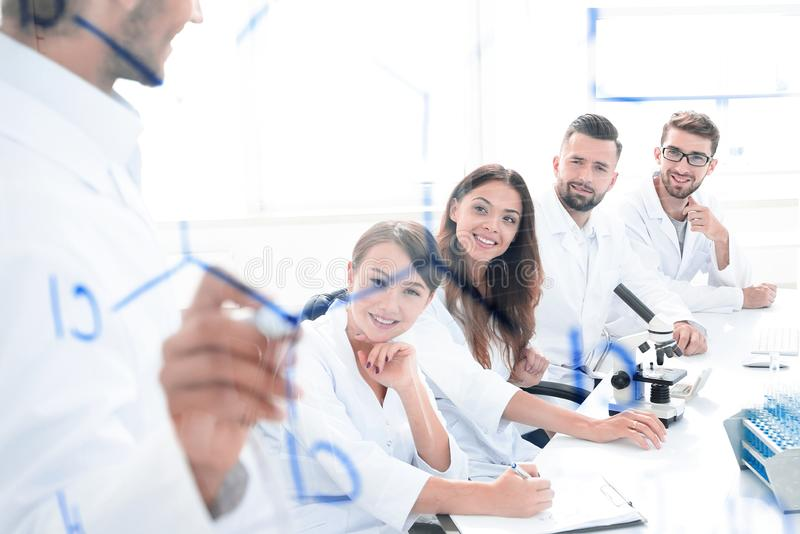 View through the transparent Board. a scientist makes a report. The concept of education royalty free stock image