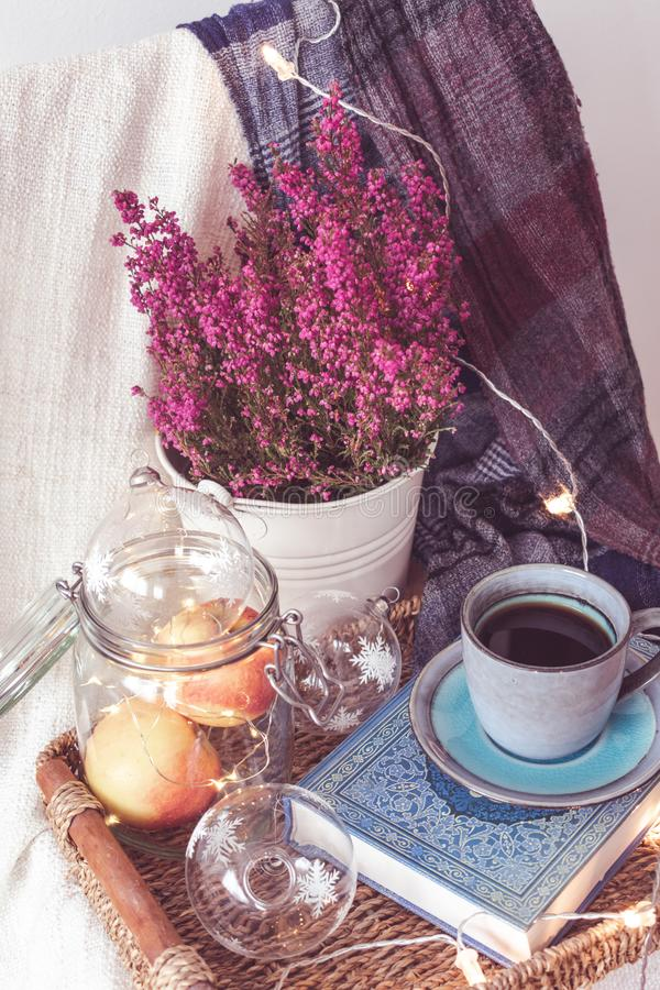A tray with a cup of coffee, apples in a jar, light chain, flowers and a scarf. View of a tray with a blue vintage cup of coffee on a book, a jar with apples stock images