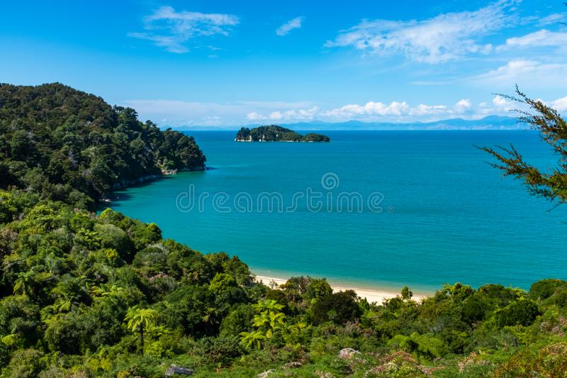 A view through the trees of a beach at the incredibly beautiful Able Tasman National Park, South Island, New Zealand. Nobody in the image royalty free stock image