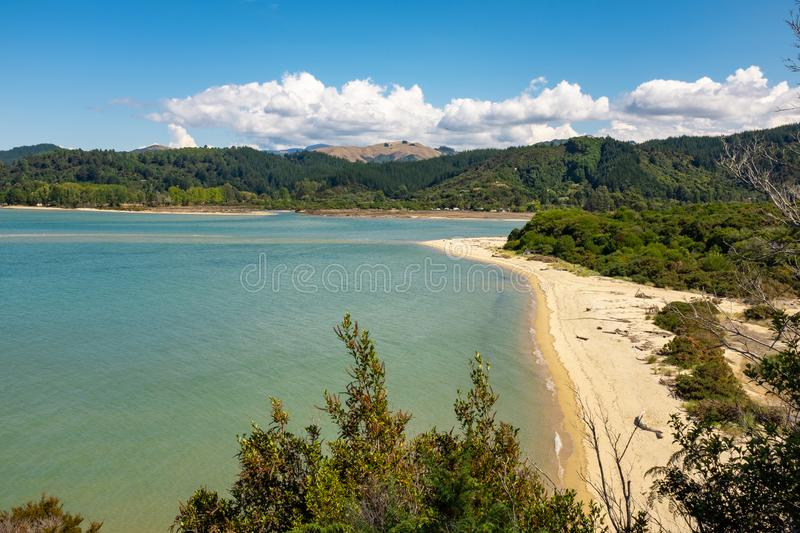 A view through the trees of an inlet and beach at the incredibly beautiful Able Tasman National Park, South Island, New Zealand. Nobody in the image royalty free stock photo