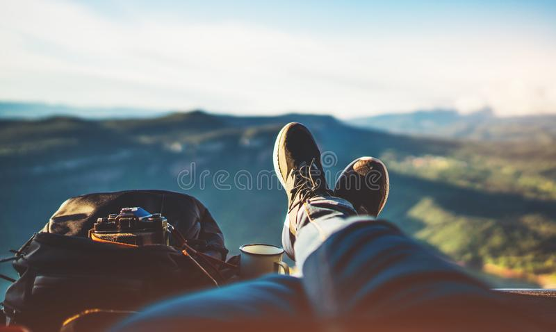 View trekking feet tourist backpack photo camera in auto on background panoramic landscape mountain, vacation concept, foot photo. Graph hiking relax in auto royalty free stock image