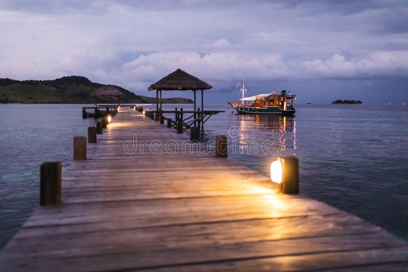 View of tropical island pier and yacht in twilight. View of tropical island, pier and yacht tourist boat standing overnight in twilight with evening lights in royalty free stock photo