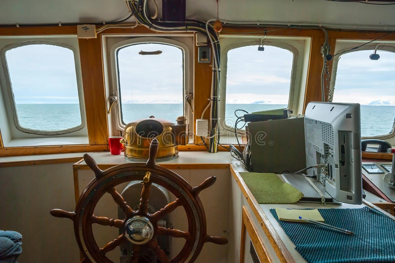 View trough capitan cabin with steering wheel on the boat. View trough capitan cabin window with steering wheen on the boat stock photography