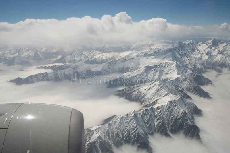 View of turbine engine and snow covered mountains from airplane window stock photos