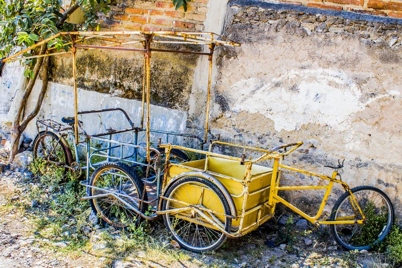 View of two abandoned cargo bicycles one blue and the other yellow. Next to a brick wall in a town of Jalisco Mexico on a sunny day stock photography