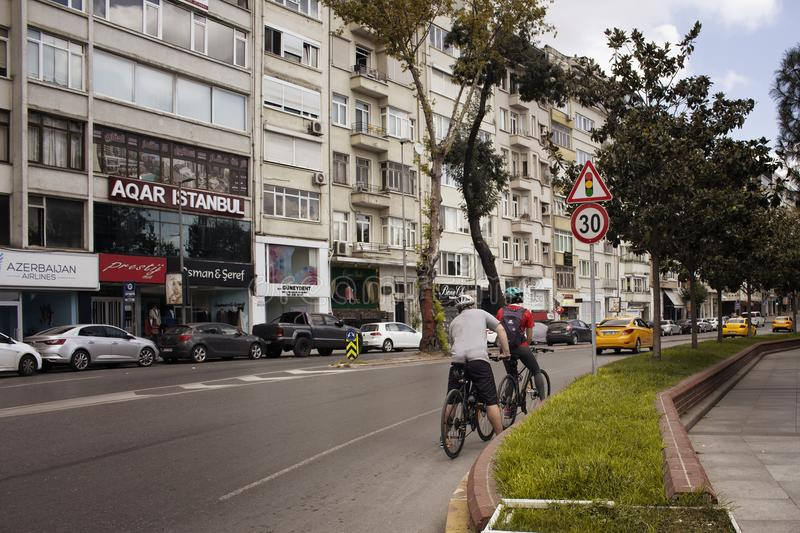 View of two bicycles riders and buildings. In the background in Nisantasi / Istanbul that is a popular shopping and residential district stock photo