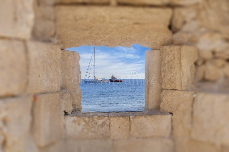 View of two boats at sea thought old castle medieval window stock image