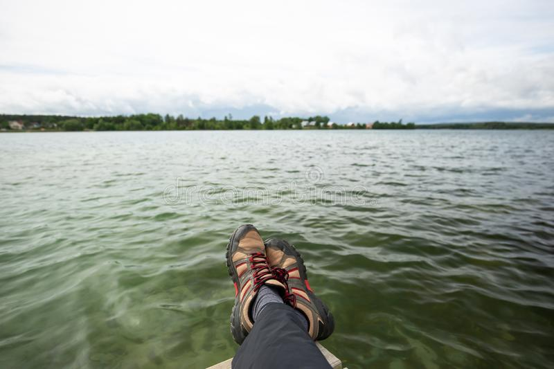View of two crossed feet and the lake and sky royalty free stock images