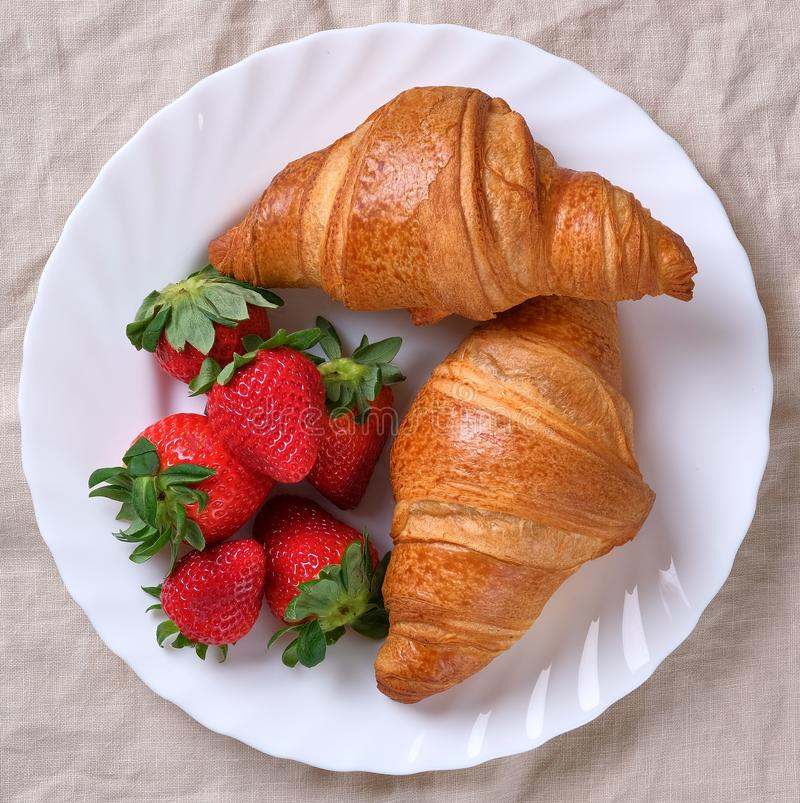 View on two fresh croissants with ripe strawberries royalty free stock photography
