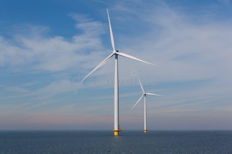 View of two windturbines in the Dutch Noordoostpolder, Flevoland and the IJsselmeer, near the town of Urk. stock photo