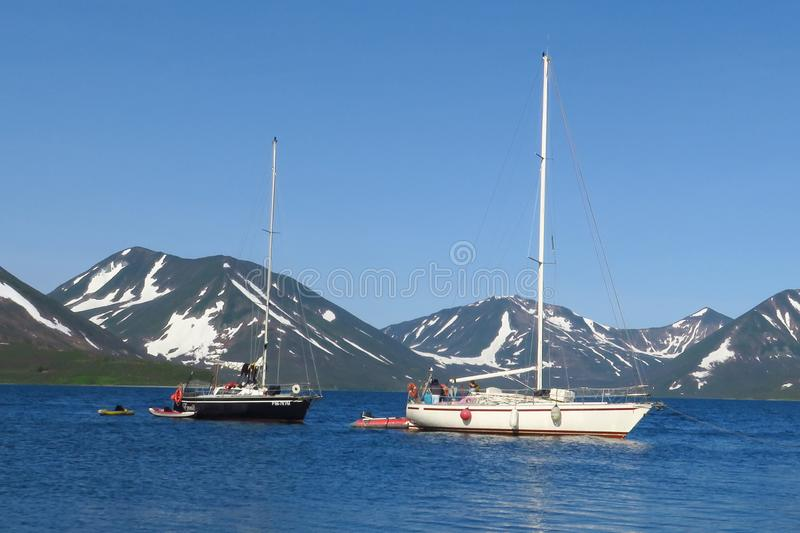 View of two yachts under the white and black sails compete in team sailing event. North Sea, blue sky and mountains as royalty free stock photography