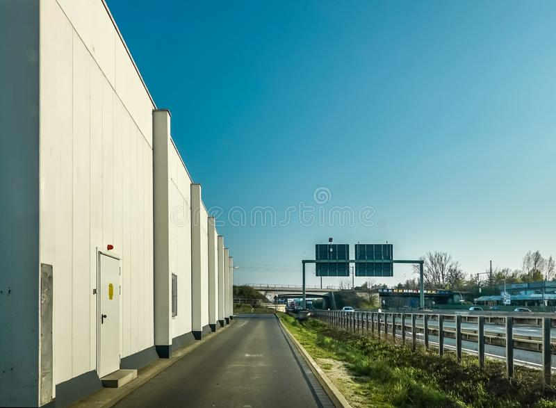 View of an ugly windowless warehouse from an asphalt road next to a motorway in Germany royalty free stock photography
