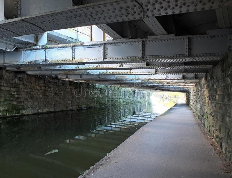 view under an old low steel girder bridge crossing the leeds to liverpool canal near armley with stone wall and a narrow footpath stock image