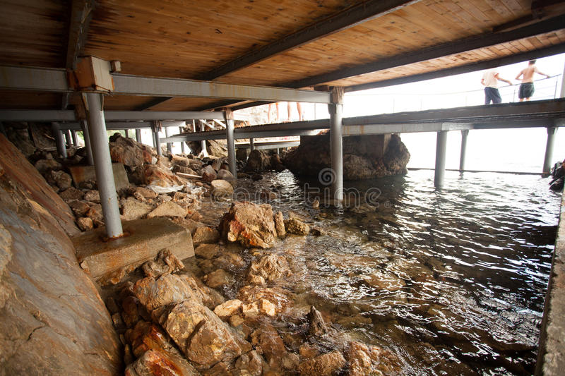 View from under the pier on shore and sea. View from under the pier on rocky shore and sea royalty free stock photo