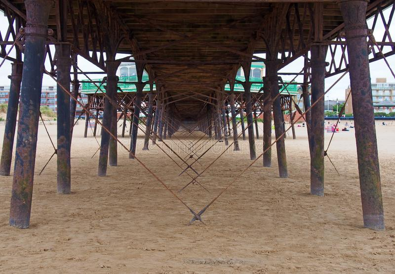 View underneath the pier showing metal supports and structure on the beach in lytham saint annes in lancashire. A view underneath the pier showing metal supports stock images