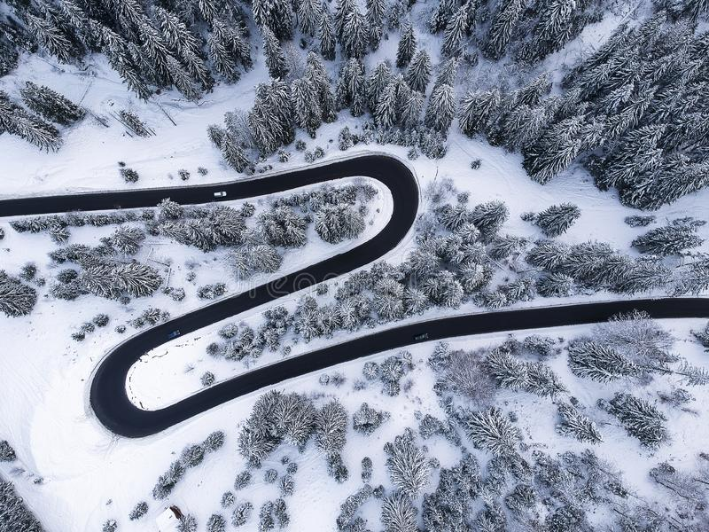 View from up of beautiful curve road in the middle of a forest full of snow in winter time stock image