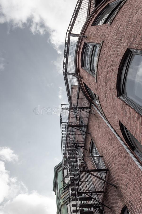 View up the face of a brick row houses with metal balconies, fire escapes against grey skies stock image