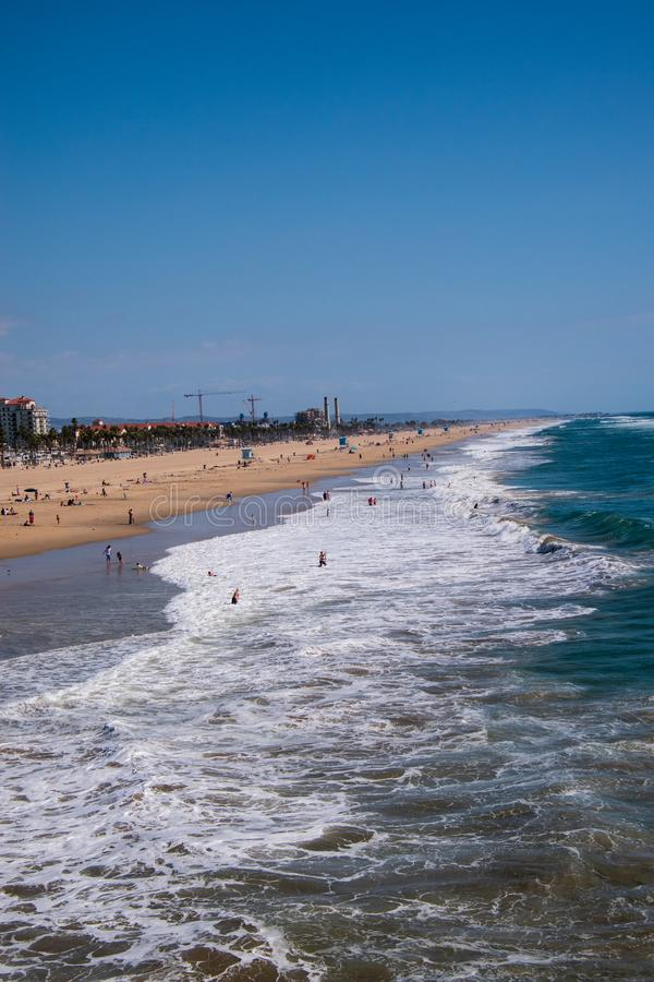 View up Huntington Beach with rough ocean with bathers and surfers. Drone view stock photos